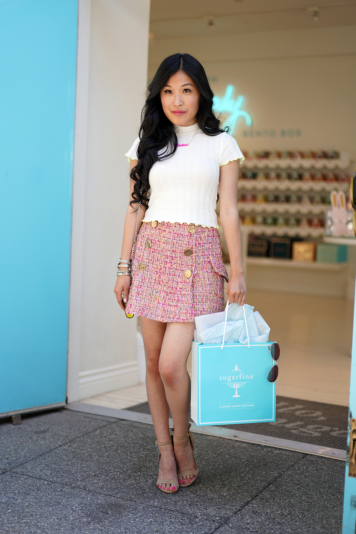 Storets Hera Tweed Classic Skirt-Pink, Topshop's Contrast Tipping Lettuce Top in white with neon edges, Moon and Lola hot pink personalized necklace saying #Kindness outside Sugarfina store