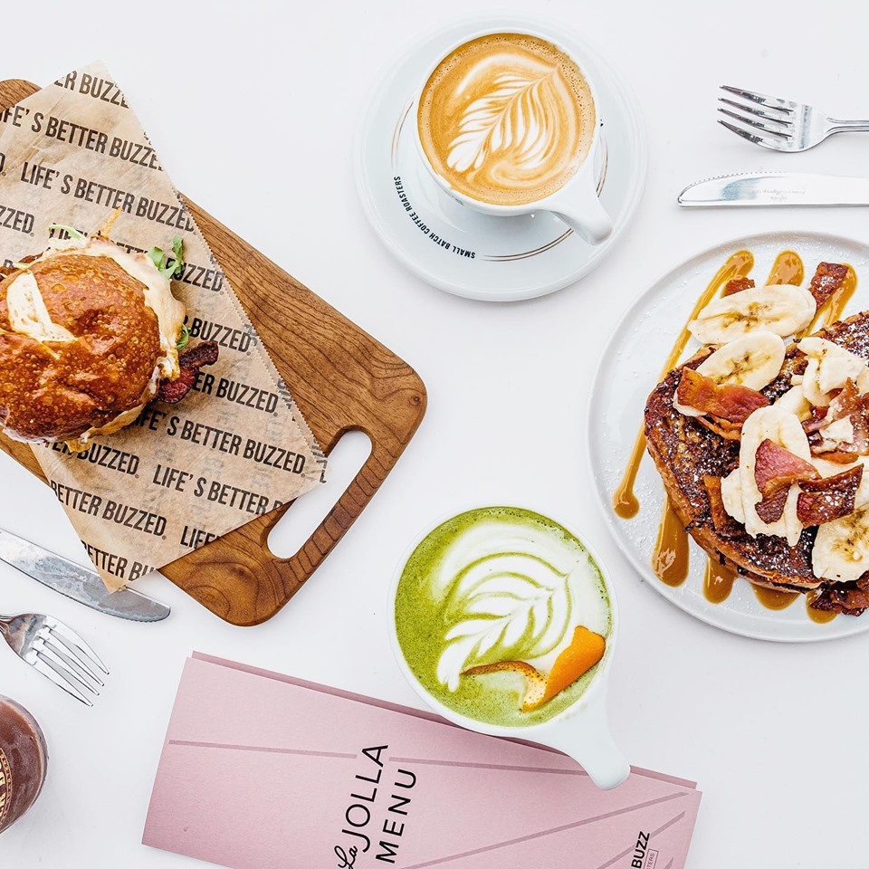 The table is set with all our brunch faves at Better Buzz La Jolla! The Triple B French Toast, Better Breakfast Sandwich, Orange Infused Matcha, and a classic Latte!