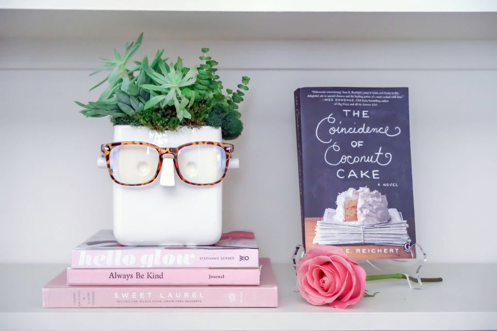 Face Plant Glasses Holder on top of pink books, The Coincidence of Coconut Cake Book by Amy E Reichert
