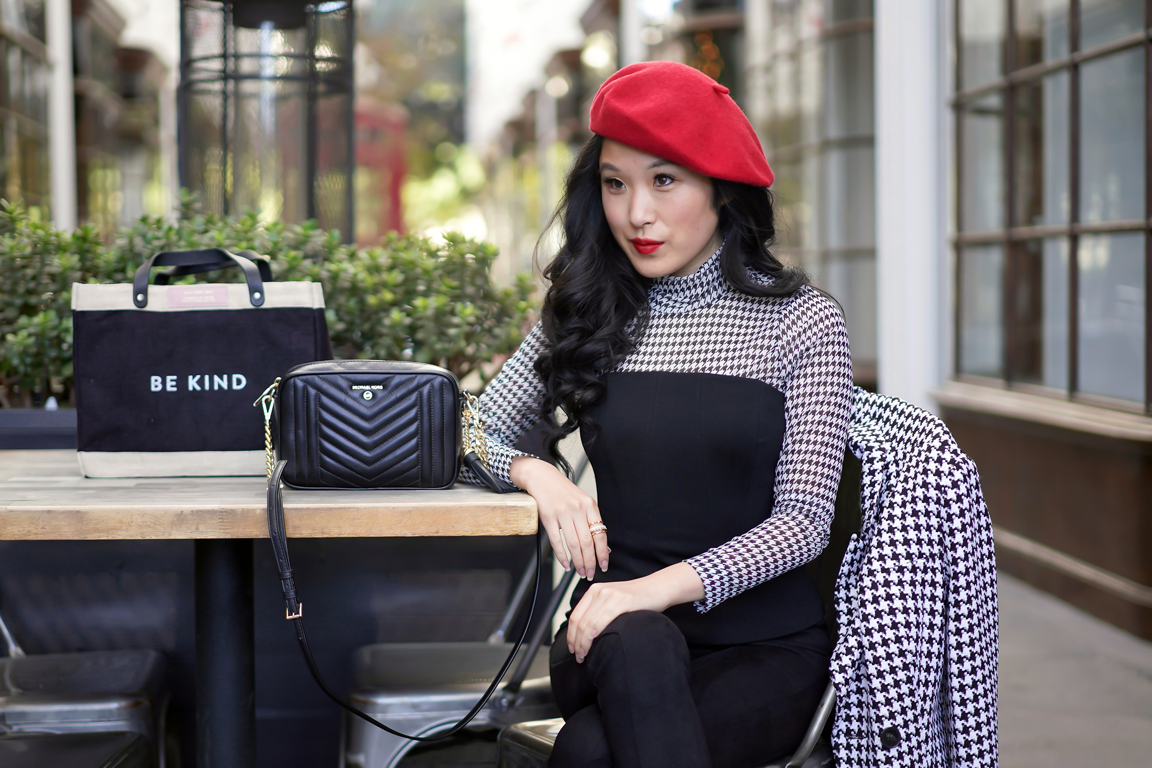 Emily In Paris - Lily Collins Inspired Fashion and Style with White House Black Market houndstooth mesh turtleneck, black bustier, red beret, Apolis bag and Michael Kors quilted camera crossbody purse